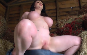 A curvy brunette with large tits is rolling around in the hay